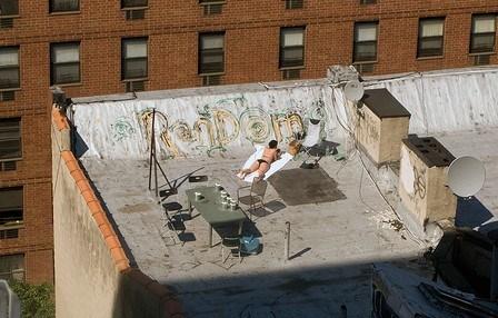 New York City woman using sunscreen rooftop