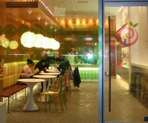 Pinkberry stores riff contemporary design stalwarts with faux ghost chairs and Saarinen-esque cafe tables