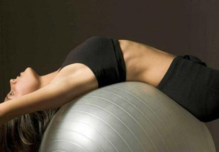 woman stretching on a Pilates ball