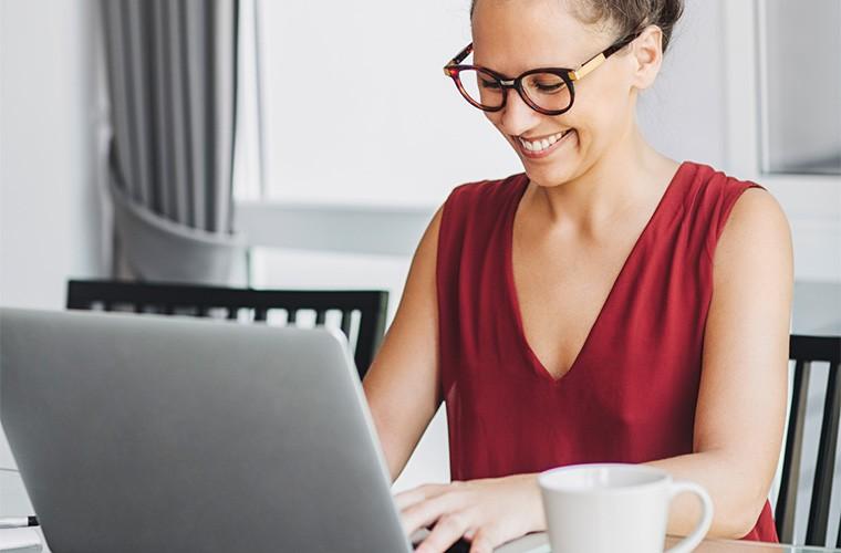 stocksy-lumina-woman-smiling-while-typing-on-laptop