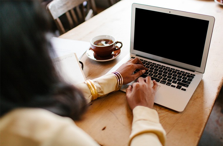 stocksy-kristen-curette-hines-woman-sitting-at-a-coffee-shop-table-working-on-a-laptop