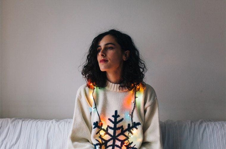 stocksy-marija-mandic-portrait-of-a-happy-woman-in-christmas-sweater