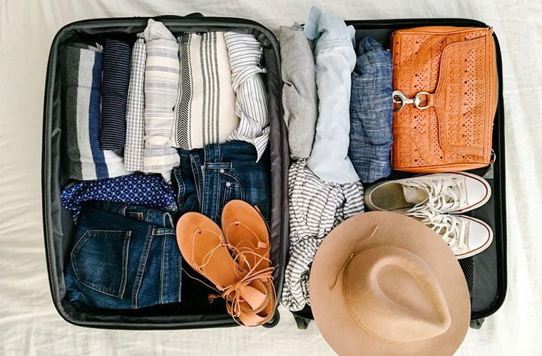 stocksy-daniel-kim-photography-suitcase-with-packed-clothes-and-accessories