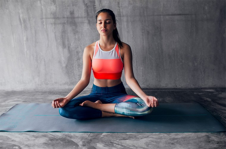 stocksy-lumina-fit-woman-meditating-indoors