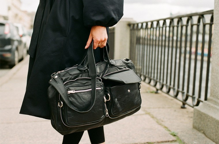stocksy-lyuba-burakova-fashionable-woman-holding-black-leather-bag