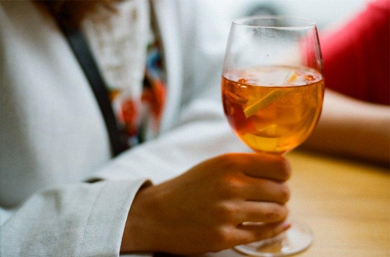 stocksy-lyuba-burakova-woman-holding-a-glass-with-spritz