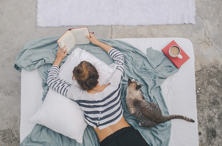 stocksy-jovo-jovanovic-woman-reading-book-while-her-cat-is-sitting-next-to-her