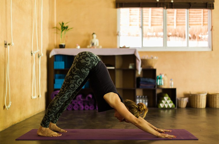 stocksy-nabi-tang-woman-doing-downward-dog-pose-in-the-studio