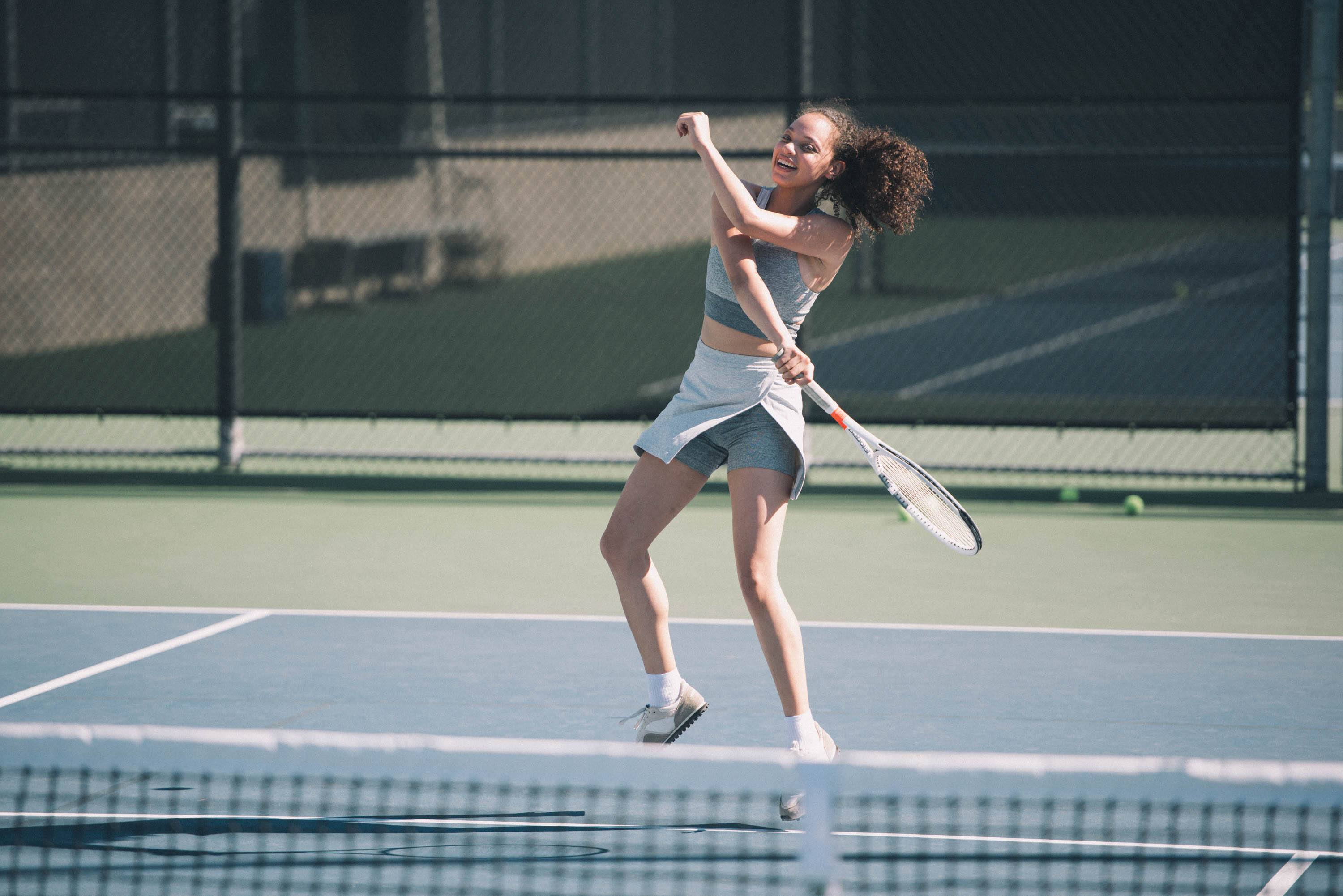 Woman playing tennis wearing workout Court Skort by Outdoor Voices