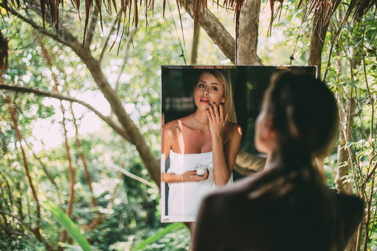 Woman putting on face cream in mirror