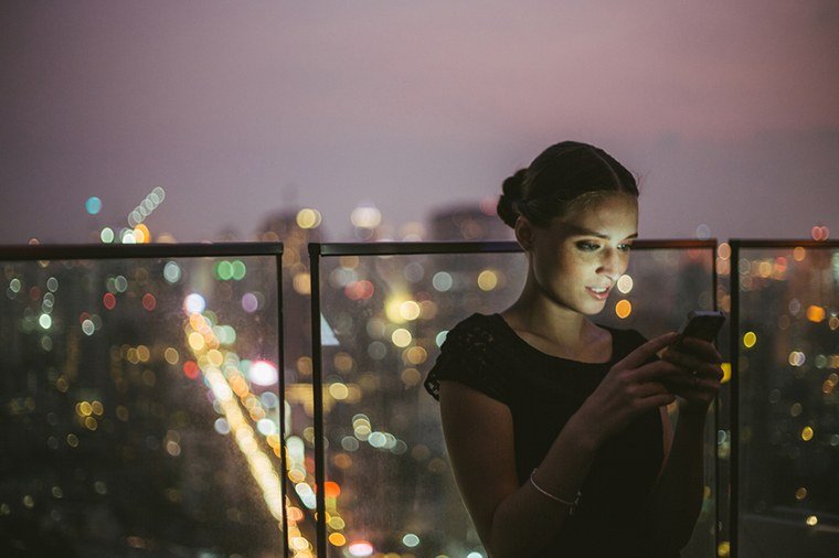 Woman looking at phone in city at night