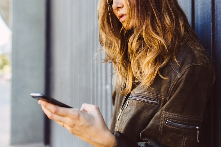 Woman in leather jacket on phone