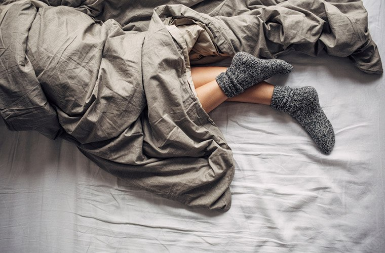 Feet in socks in bed