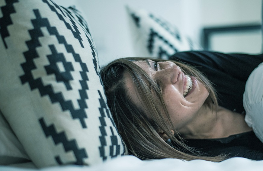 Woman laughing in bed