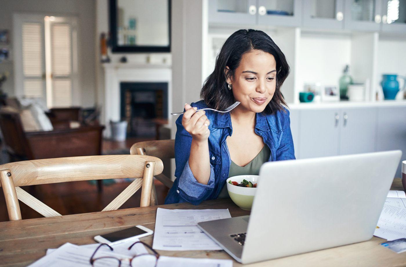 woman at computer eating salad